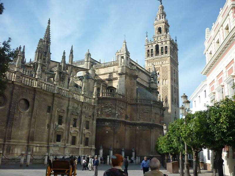 La fachada este de la catedral de Sevilla, con la Giralda, desde la plaza del Triunfo
