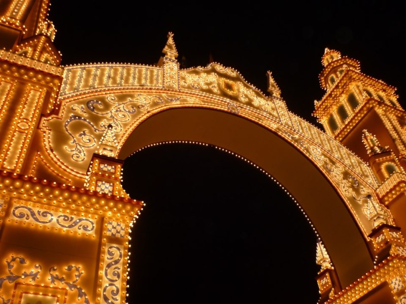 La portada de la Feria de abril de Sevilla 2013 está inspirada en la Plaza de España, conmemora el 75 aniversario de la fundación de la ONCE, y hace también alusión a la Hermandad del Rocío de Triana, que cumple su segundo centenario este año.